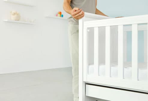 Man standing beside crib in nursery