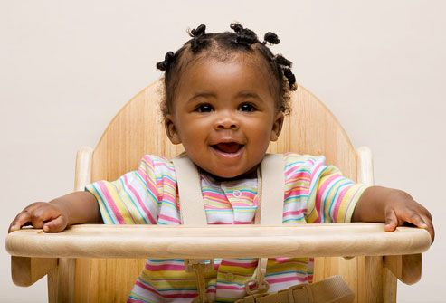 Happy baby girl in high chair