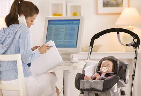 Mother working at computer with baby in stroller