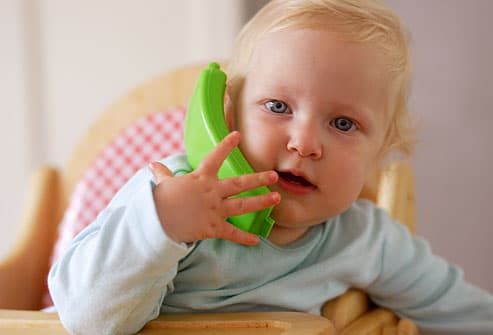 Baby talking on toy telephone