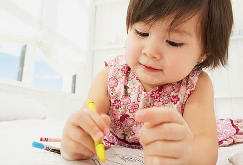 toddler scribbling with yellow crayon