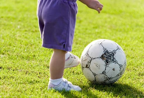 toddler kicking a soccer ball