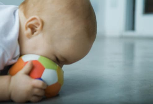 baby chewing on ball