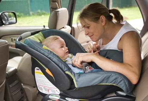 mother securing baby in car seat