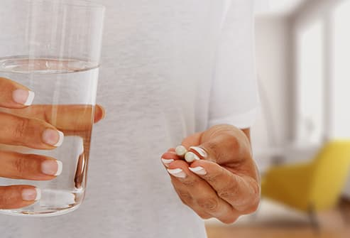 woman holding glass of water and medication