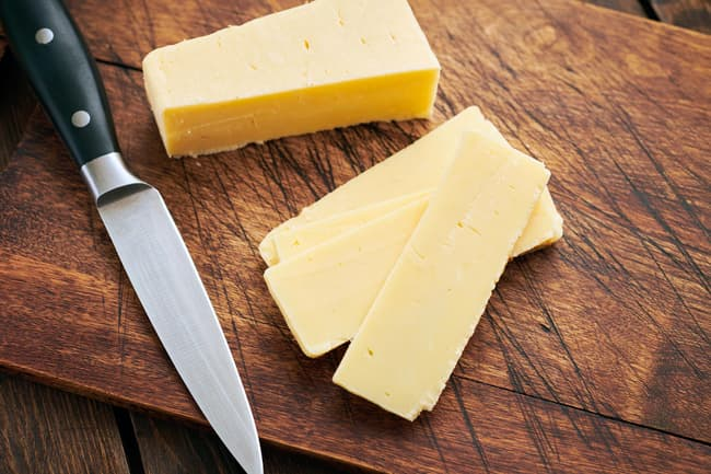 photo of sliced cheddar cheese on cutting board