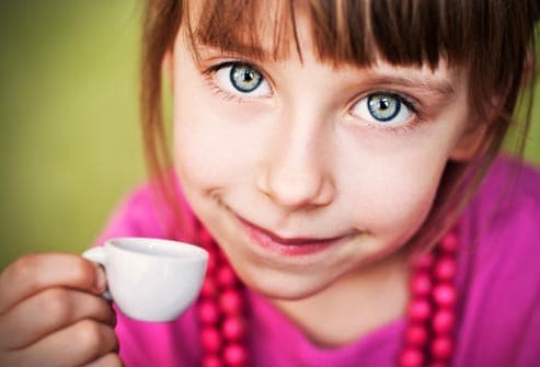 young girl holding tiny cup