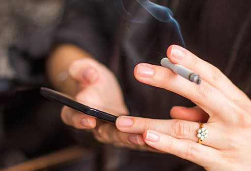 woman smoking with smartphone close up
