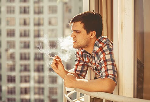 man smoking on balcony