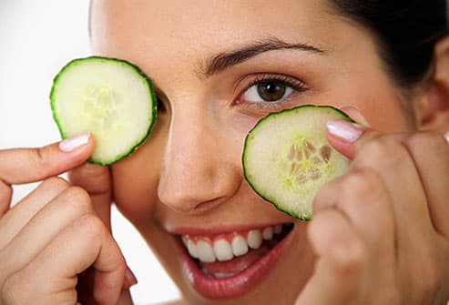 woman putting cucumber on eyes