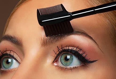 woman using eyebrow brush