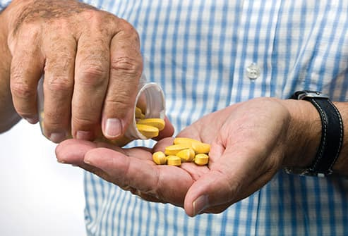 man pouring pills into hand