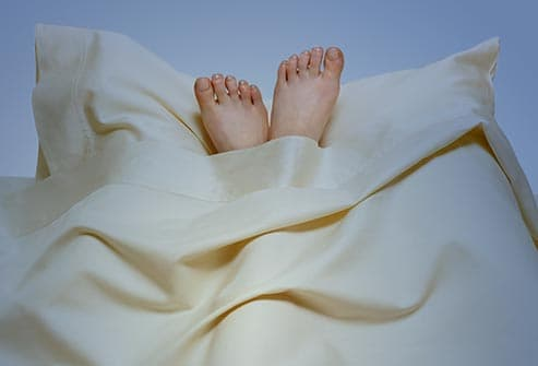 woman with feet on pillow