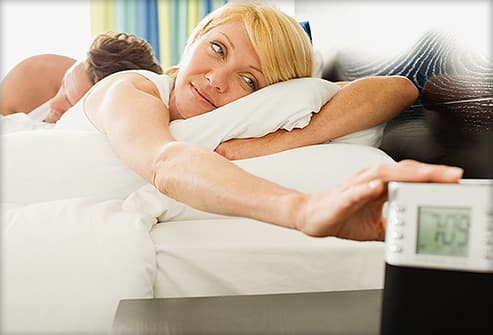 woman hitting snooze button