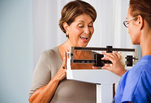 smiling woman on weight scale