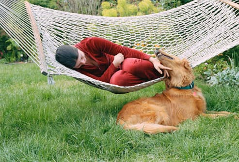 Woman on hammock petting dog