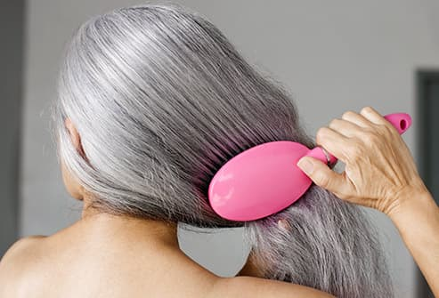 senior woman brushing her hair