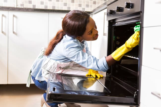 photo of woman cleaning oven