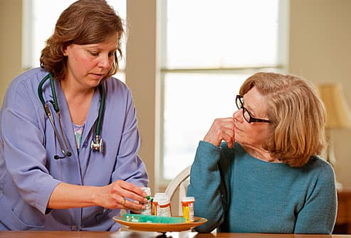 Healthcare worker helping with woman with meds