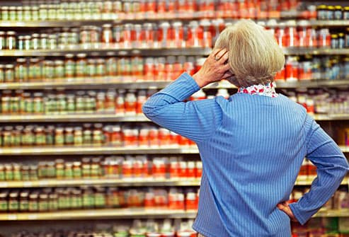 Woman having trouble reading labels in store