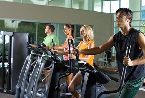 people working out on elliptical trainers