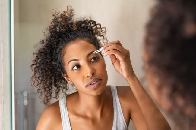 photo of woman plucking eyebrows