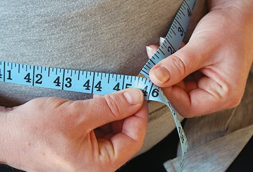 man measuring stomach