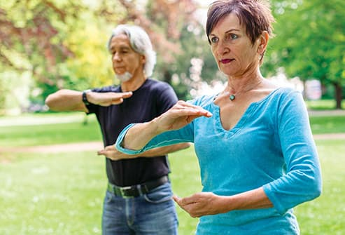 senior couple doing tai chi in park