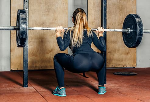 woman doing squats in gym