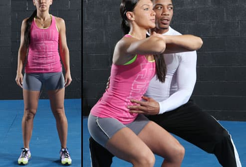 Trainer Helping Woman With Squat Exercise