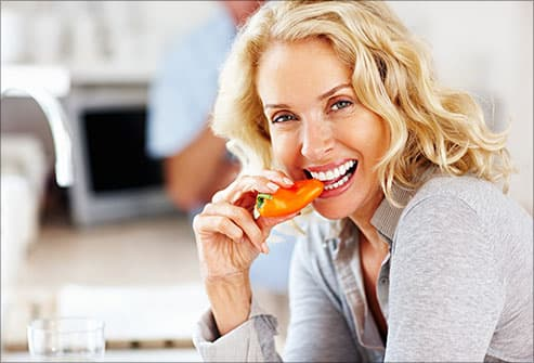 woman eating a red bell pepper