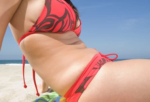 Girl in bikini at beach with closeup of abdomen