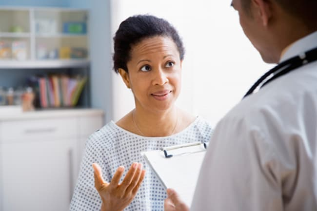 photo of woman talking with doctor