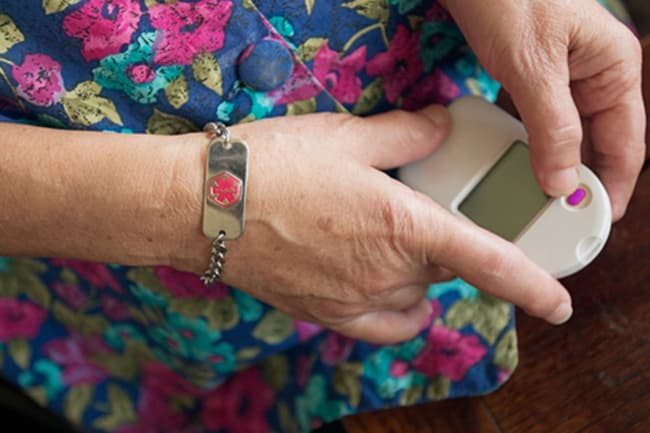 photo of woman using glucose meter