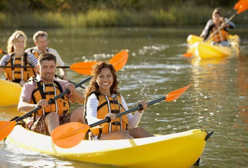 Group of Couples Paddling in Kayaks