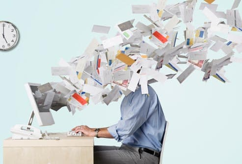 businessman covered in flying paperwork
