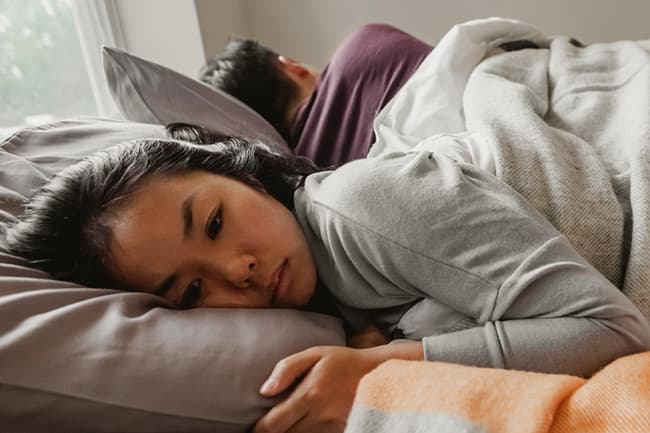 photo of unhappy woman in bed
