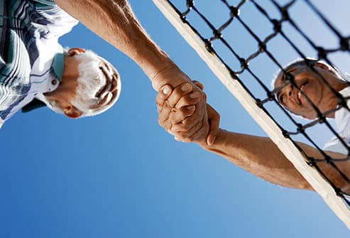 to men shaking hands over tennis net