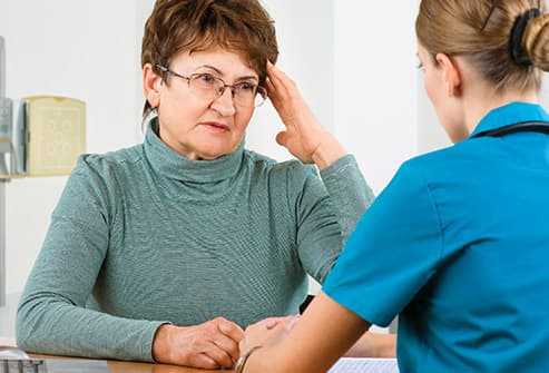 mature woman describing headache to doctor