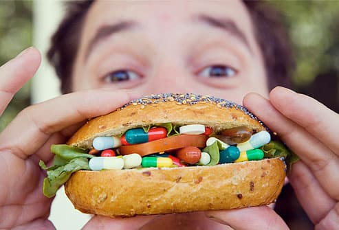 Man eating sandwich of pills and capsules