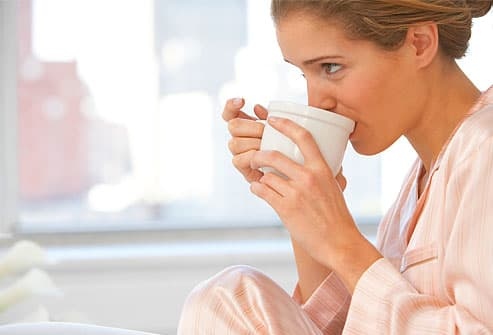 Young woman wearing pajamas, drinking coffee