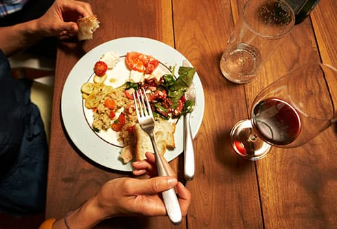 woman drinking wine with meal