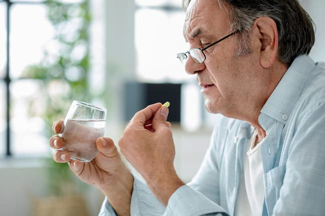 photo of man taking pill