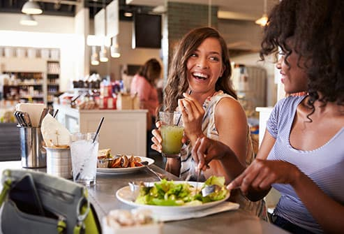 women laughing eating salad