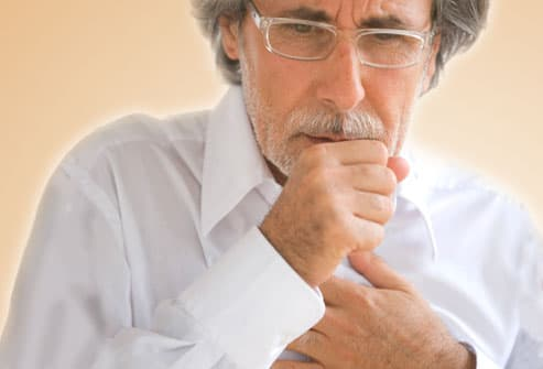 Man holding chest and coughing