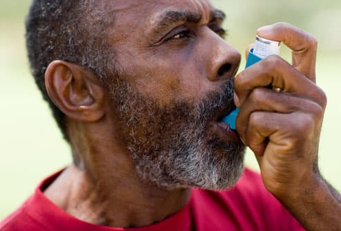 Older man using inhaler