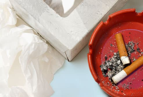 Cigarette butts in ashtray next to kleenex