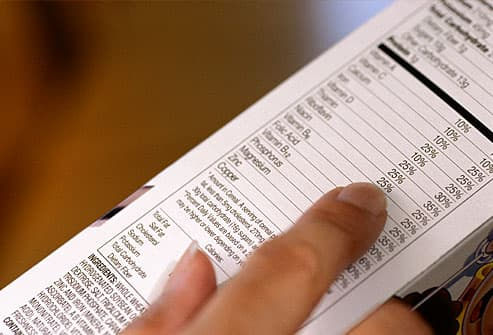 Close up on woman reading nutrition label