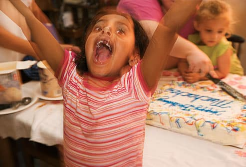 Hyper girl in front of birthday cake