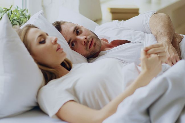 photo of couple having conversation in bed